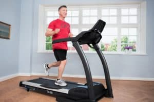 Man running on treadmill at home